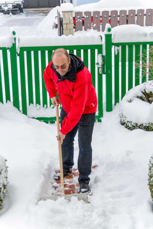 onset: a man shoveling the new snow from a path. onset of winter Stock Photo