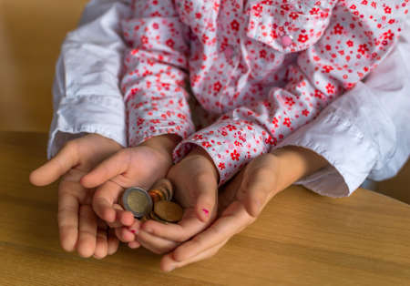 assessment system: children hold coins of money in their hands. symbolfoto learn for saving and handling money.