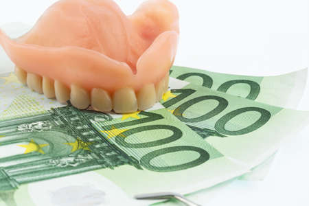 surgery costs: dentition and euro notes, symbolic photograph of dentures, treatment costs and payment