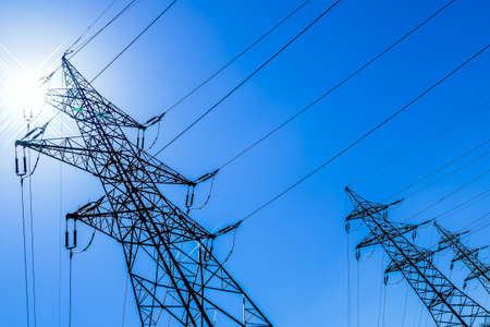 voltage: the utility pole of a high voltage line. symbol photo for energy. against blue sky Stock Photo