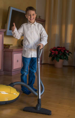 putz: a boy draws a vacuum cleaner living room. children while brushing Stock Photo