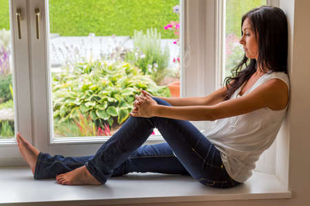 psychologically: a young woman sitting on window and relaxes