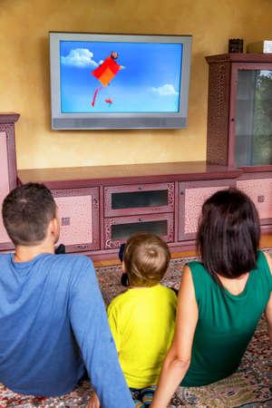 ver tv: familia que se sienta delante de un televisor y ver un programa infantil en. Foto de archivo