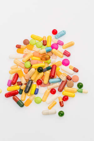 therapie: many colorful pills on white background. symbol photo for medicine and drugs