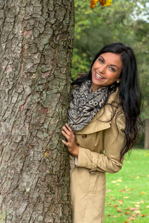 vivre: a young woman looks out from behind a tree Stock Photo