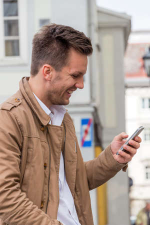 mobile communication: a man writes on his mobile phone an sms. communication with a smart phone