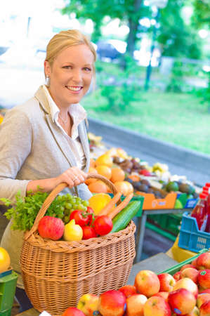 congenial: a young congenial woman buying fruits and vegetables at a fruit market Stock Photo