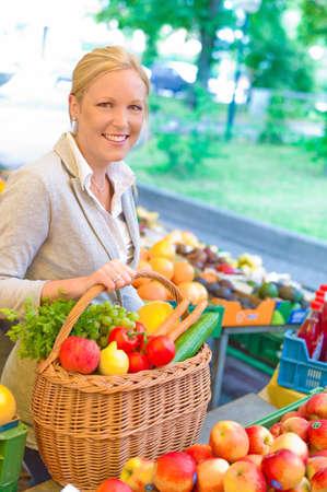 gamme de produit: une jeune femme sympathique acheter des fruits et des l�gumes � un march� de fruits Banque d'images