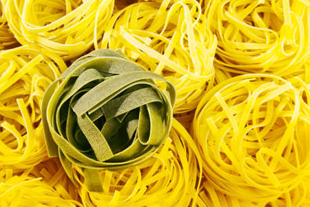 adjacent: uncooked pasta nests are adjacent. tagliatelle from italy. Stock Photo