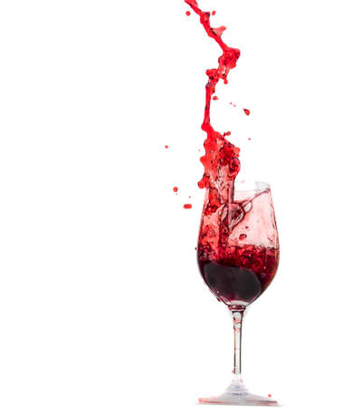 glass of red wine: red wine being poured from a wine glass. wine in the wine glass. Stock Photo