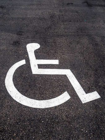 wheelchair users: a wheelchair is mounted on a car park for handicapped. Stock Photo