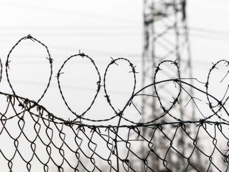 remand: a fence is secured with barbed wire. symbol photo for security, prison and crime. Stock Photo