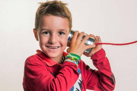 notieren: child listens to a dosentelefon.
