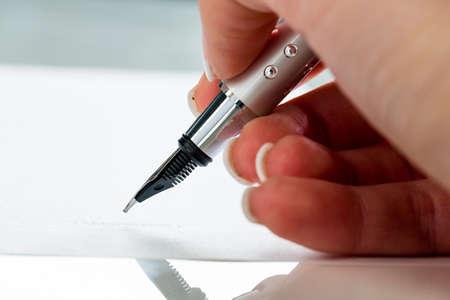 testament schreiben: eine Hand mit einem F�llfederhalter in untrerschrift im Rahmen eines Vertrags oder Testament.