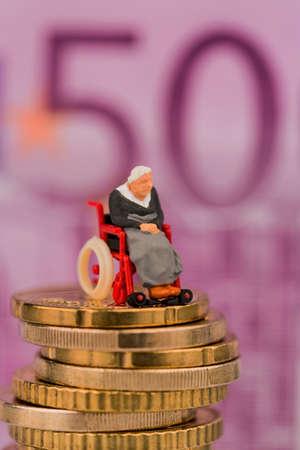 salud publica: mujer en silla de ruedas en la pila de dinero, la foto s�mbolo para la asignaci�n de asistencia discapacidad y costos en salud p�blica Foto de archivo