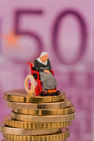 woman in wheelchair on money stack, symbol photo for disability care allowance and costs in public health Stock Photo
