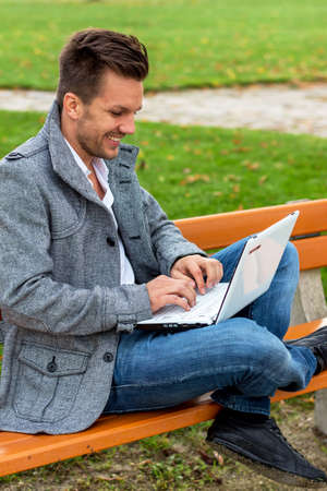 edv: a man with a laptop sitting on a park bench Stock Photo