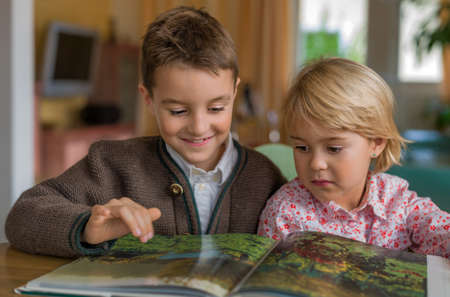 relaxen: two children look at a book together on Stock Photo