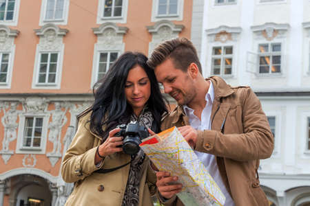 guide: young couple with a map and guide during a tour of town on vacation