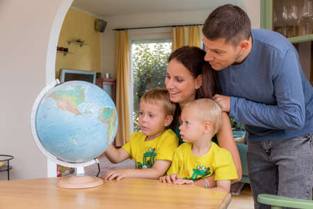 world globe map: a family sitting at a globe and planning a trip in the holidays