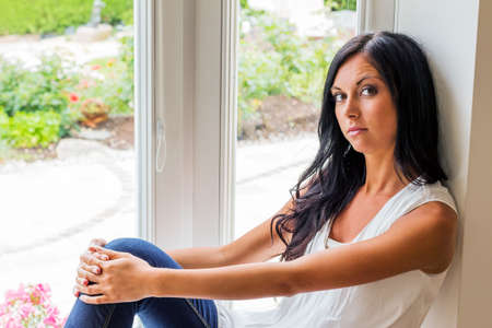 woman window: a young woman sitting on window and relaxes