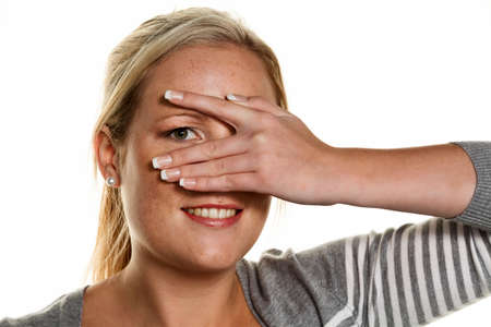 shrewd: a young woman looking through her fingers in her hand. symbol photo for perspective and flirt