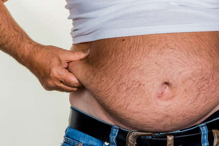 constrict: man with overweight. symbol photo for beer belly, unsuccessful dieting and poor nutrition.