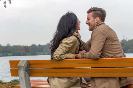 vivre: a young, laughed liebtes couple sitting on a park bench