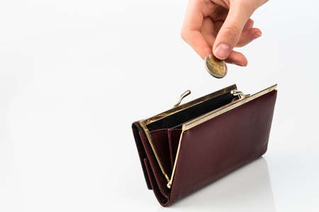 subsistence: an empty purse and a hand which holds a coin in front of a white background Stock Photo