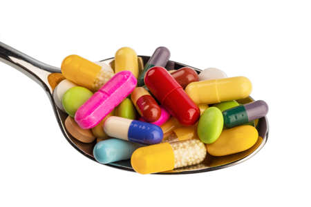 many colorful pills on a spoon. symbol photo for painkillers and abuse of drugs.