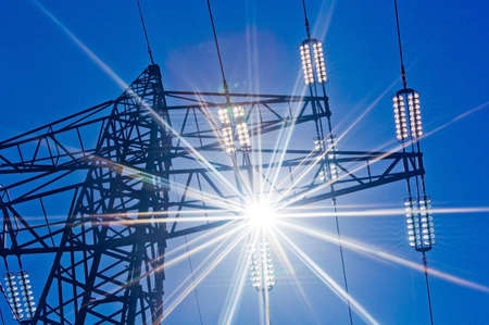 a pylons for electricity against a blue sky and sun rays