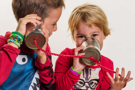 hark: two little kids calling with a phone of two doses. Stock Photo