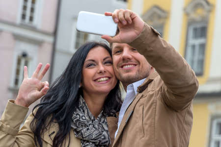 dear: a young couple making a self-portrait with a cell phone. selfies are in.