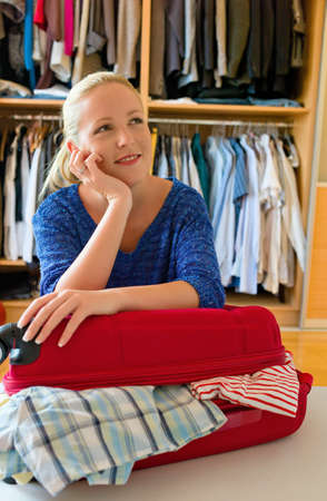 holydays: a young woman is packing her suitcase for the trip to the holiday.