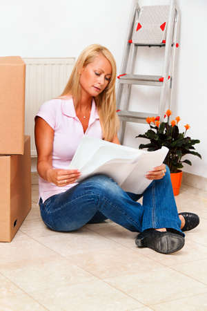 house exchange: woman with cardboard boxes on moving to the new apartment.