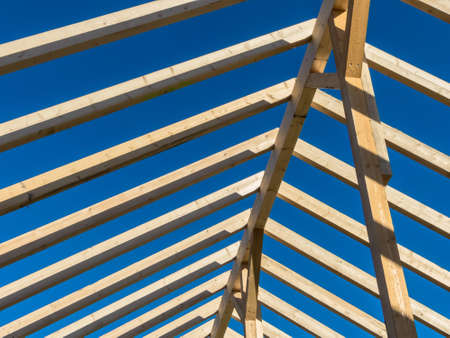financed: in a house with a new roof is being built on a construction site. carrier wooden roof truss. Stock Photo