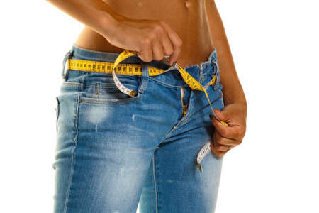 thinness: a young, slim woman in jeans with a tape measure after a successful diet