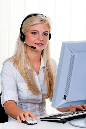 young woman with headset and computer at hotline. friendly clerk photo