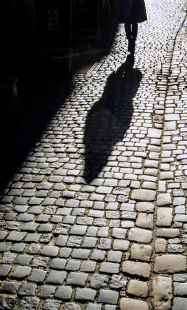 fleeing: the shadow of a woman on the street. Stock Photo