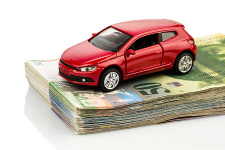 a car is on swiss franc bills. costs for the purchase of automobiles, gasoline, insurance and other car costs Stock Photo