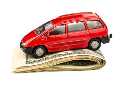 a car standing on dollar bills. costs for the purchase of automobiles, gasoline, insurance and other car costs