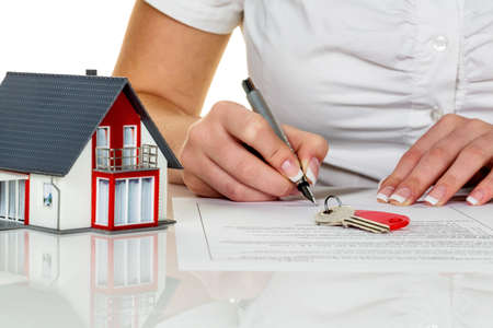 immobilien: a woman signs a purchase agreement for a home with a real estate agent. Stock Photo