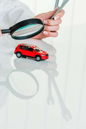 a model of a car is examined by a doctor. symbol photo for workshop, service and car purchase.