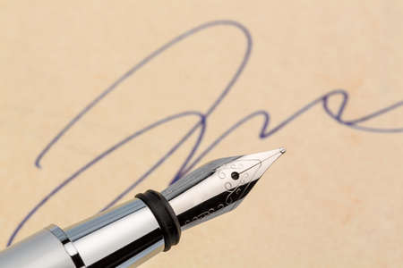 notieren: a signature and a fountain pen on yellow paper. symbol photo for contract, testament and graphology Stock Photo
