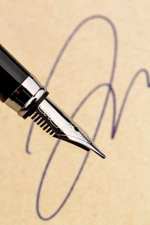 testament schreiben: eine Unterschrift und einen Füllfederhalter auf gelbem Papier. Symbol Foto für Vertrag, testament und Graphologie Lizenzfreie Bilder