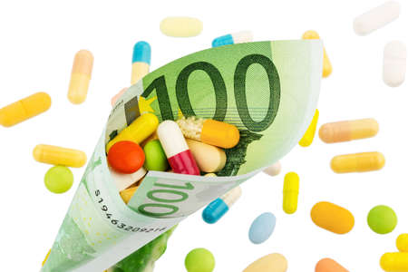 physican: tablets and one hundred euro bill symbol photo: cost of medicine and drugs in the pharmaceutical industry Stock Photo