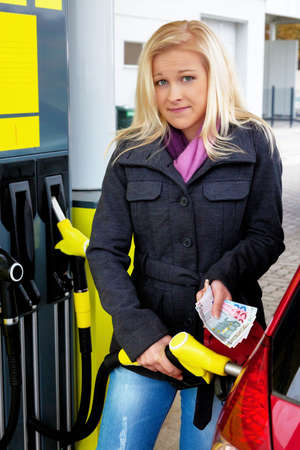 pkw: a young woman tank gasoline on a gas station. the cost of the car are due to gasoline prices more expensive