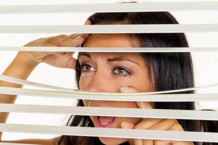 blinds: a young woman watching something through the blinds of her window Stock Photo