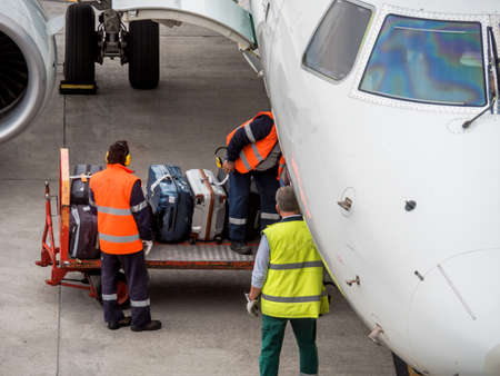 baggage: an aircraft is docked at an airport. suitcases are loaded