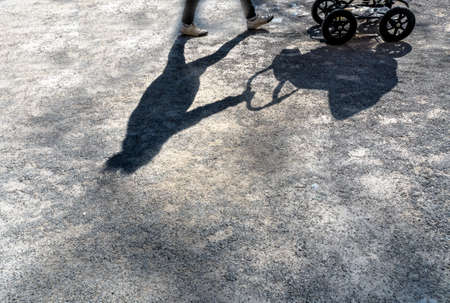 woman shadow: shadow eirn woman with a stroller.